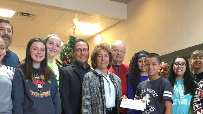 """Students of Red Mountain Middle School's National Junior Honor Society handed a $1,000 donation to Cancer Support of Deming & Luna County on Friday, Dec. 9, 2016. The students began raising money in October for the local cancer organization which helps community members with their battle against cancer by providing transportation and comfort for the patients. After selling bracelets, necklaces and other items, the students handed over a check for the first time for the organization and plans to help local """"Cancer Warriors"""" in the future."""