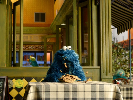 Cookie Monster enjoys a snack outside of the re-designed Mr. Hooper's Store.
