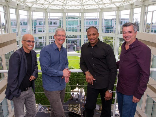In this image provided by Apple, from left to right, music entrepreneur and Beats co-founder Jimmy Iovine, Apple CEO Tim Cook, Beats co-founder Dr. Dre, and Apple senior vice president Eddy Cue pose together at Apple headquarters in Cupertino, Calif.