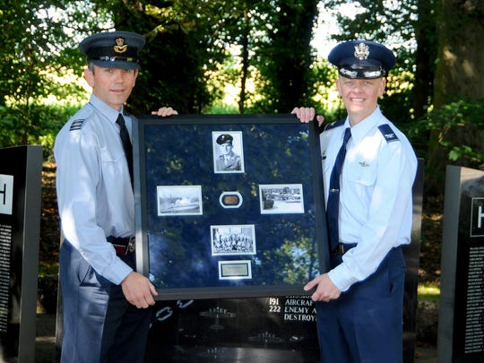 Wing Commander Cornish, officer commanding support wing, Royal Air Force Honington and U.S. Air Force Col. Derek Salmi, 100 Air Refueling Wing, Operations Group commander pose in front of the 388th Bombardment Group (Heavy), 8th AF memorial with the framed WWII U.S. Army Air Forces dog tag that was found while metal detecting on the former RAF Knettishall (US Air Base 136) near Knettishall, U.K., Aug. 12, 2016. This repatriation of the U.S. service member's dog tag marked the official receipt from the RAF to the USAF on behalf of the surviving USAAF service member who was assigned to the 388th BG, 8th AF and is currently living in Louisiana. Following this ceremony, the dog tag will be transported to the 8th AF in Louisiana where it can then be officially presented to its rightful owner. (U.S. Air Force photo by Senior Master Sgt. Brian M. Boisvert)