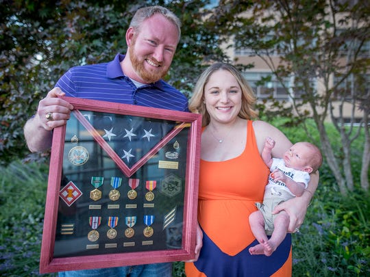 Former U.S. Army Staff Sgt. Jeff Fulton and family with his military shadow box, displaying his awards.