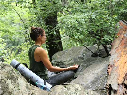 A participant in recent Namaste in Nature class meditates near Catawba Falls in Pisgah National Forest.