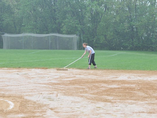 Girls' softball Heah Coach Karyn Albaneius trying to get the field ready early on a Saturday morning in 2009.