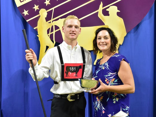 John Henderson, East Troy, Wis. (left) won fifth place showmanship honors at the 2018 National Junior Angus Showmanship Contest, held in conjunction with the National Junior Angus Show (NJAS), July 7-13 in Madison, Wis. Also pictured presenting the Silver Revere bowl is Julie Murnin, American Angus Auxiliary advisor. The top five winners also received a monetary award from the Ham James Memorial Fund. Forty-seven youth from across the country and Canada competed for top honors in the 52nd annual event.
