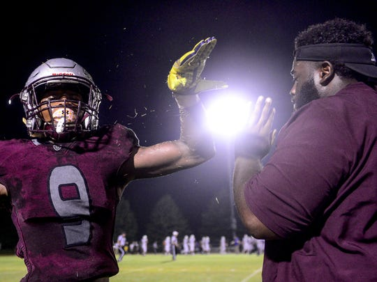 Liberty's Saidrick Pewitte high fives a coach at the