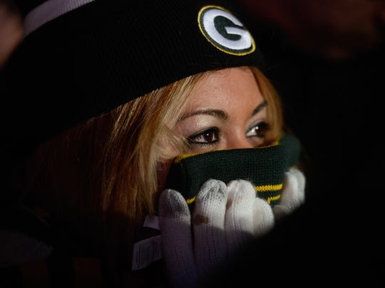Priscilla Tafolla, of Weslaco, Texas, shields her face from the cold while watching the Packers playoff pep rally in front of the Oneida Gate at Lambeau Field.