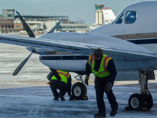 A ground crew from Heritage Aviation secures a plane after it arrived at the company's terminal at the Burlington International Airport in South Burlington on Wednesday, January 13, 2016.