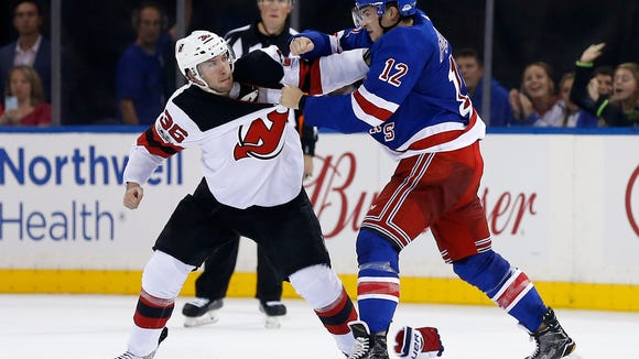 New Jersey Devils right wing Nick Lappin (36) fights with New York Rangers left wing Matt Puempel (12) during the second period of an NHL preseason hockey game Wednesday, Sept. 20, 2017, in New York. (AP Photo/Adam Hunger)