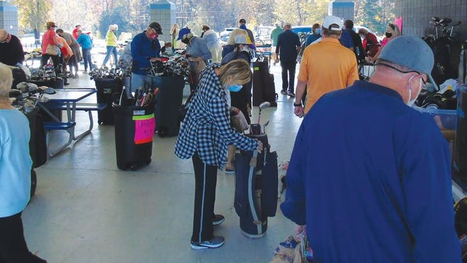 Shoppers, abiding COVID-19 restrictions, were busy choosing from many golf accessories.