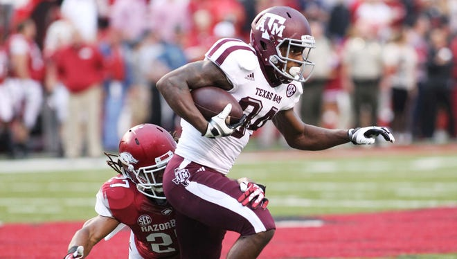 Texas A&M wide receiver Malcome Kennedy (84) runs after a catch as Arkansas  safety Alan Turner (27) attempts a tackle during the first quarter Saturday at Donald W. Reynolds Razorback Stadium.