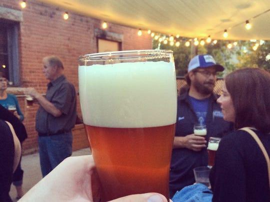 A glass of Crowdsource Fresh Hop Ale, a pale ale beer featuring various hop varieties.