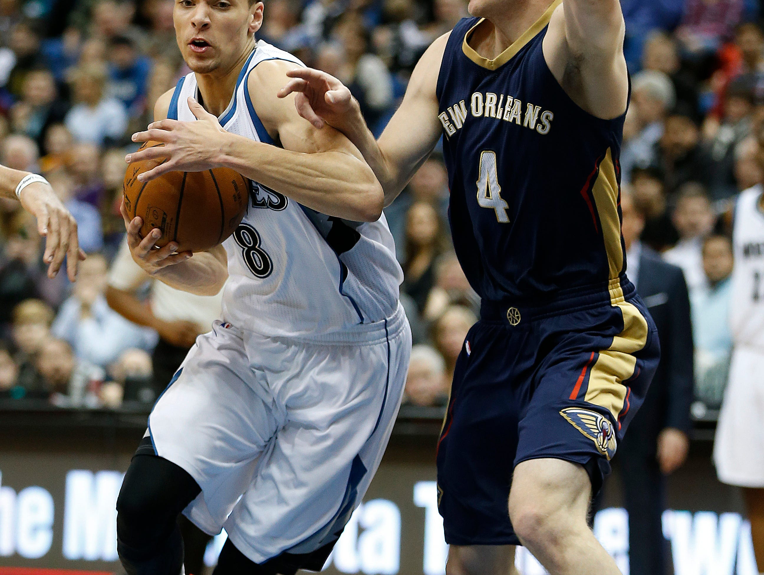 Minnesota Timberwolves guard Zach LaVine (8) moves past New Orleans Pelican guard Nate Wolters (4) during the second half of an NBA basketball game, Friday, Jan. 23, 2015, in Minneapolis. The Pelicans won 92-84. (AP Photo/Stacy Bengs)