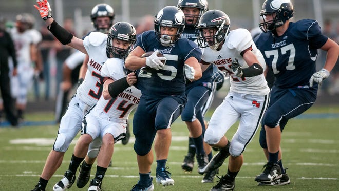 Marysville senior Dante Chrcek runs the ball and breaks through a host of Marine City defenders during a football game Friday, September 16, 2016 at Marysville High School.