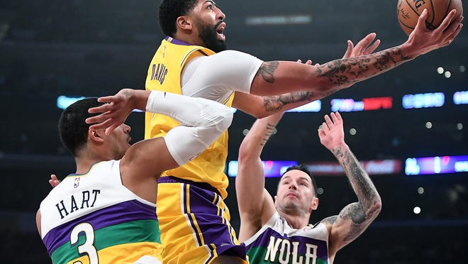 The Los Angeles Lakers' Anthony Davis, middle, drives to the basket between the New Orleans Pelicans' Josh Hart (3) and J.J. Redick in the first quarter at Staples Center in Los Angeles on Tuesday, Feb. 25, 2020.