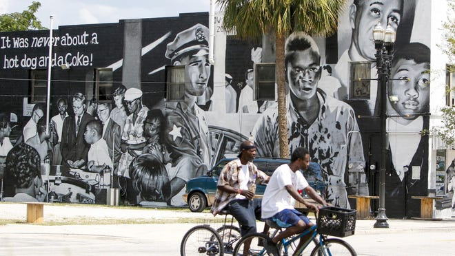 """People bike past a mural on the Eastside Brotherhood Club building that depicts """"Ax Handle Saturday"""" on Thursday, June 18, 2020 in Jacksonville. The Republican National Convention is scheduled to happen on the 60th anniversary of the day that the painting refers to, when African American teenagers were met with violence for sitting at a then segregated diner."""