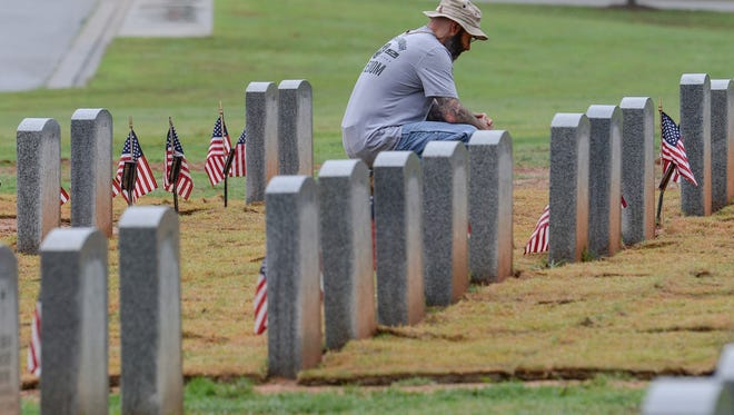Alan Turrett of Easley, U.S. Army veteran who served from 1997 to 2000 looks at one of the many gravestones which flags were placed for Memorial Day at Dolly Cooper Cemetery in Anderson on Friday. Friends of Veterans and Road U.S. Military Vets motorcycle club placed flags on 399 graves of military veterans at the cemetery.