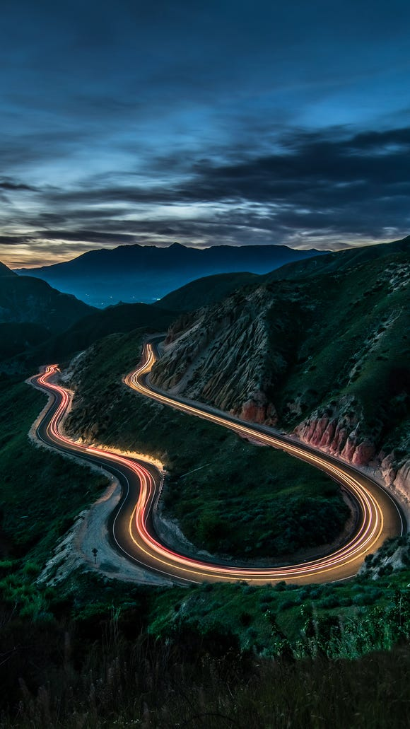 A long exposure creates strands of light as cars wind around Grimes Canyon Road.