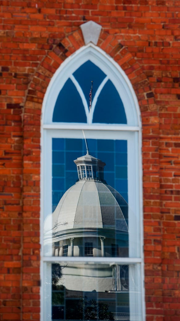 The state capitol building reflected in a window of