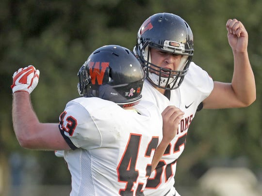 West De Pere running back Austin Beaumier celebrates with teammate Cameron Reese after Beaumier scored against the West Wildcats Friday September 1, 2017 at West High School in Green Bay, Wis.