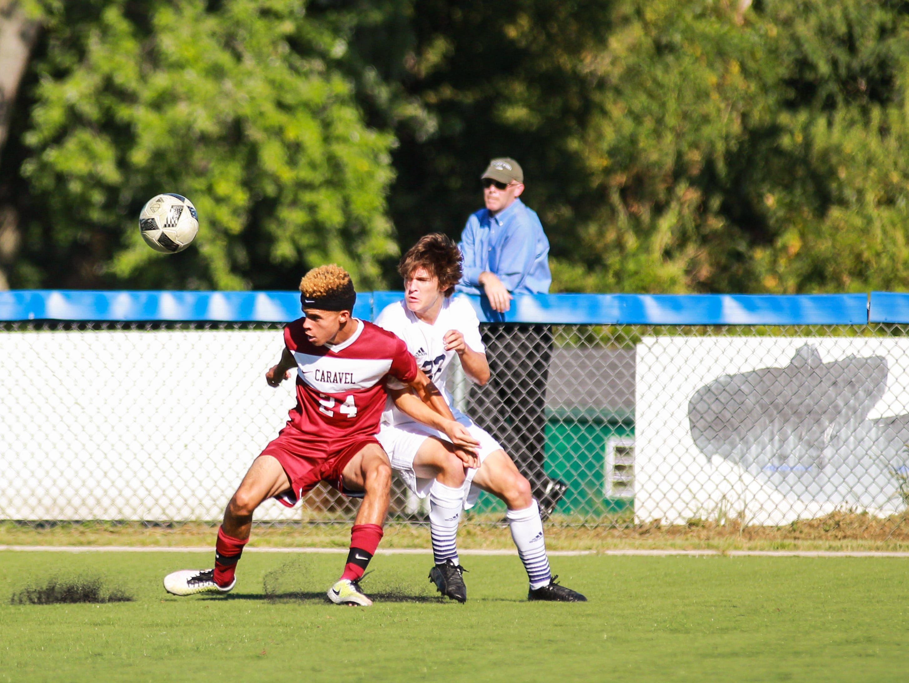 Caravel's Austyn Hamilton (24) tries to keep Salesianum's Aiden Kelly (23) from gaining control of the ball in the Sals' 7-0 win over Caravel on Tuesday.