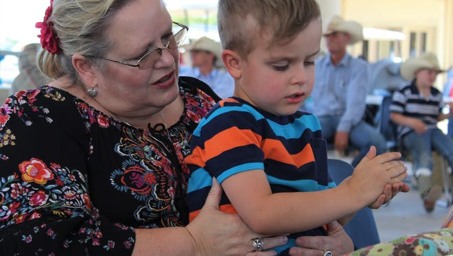 """Donna Gore was at the merchandise table Friday at the Western Heritage Classic, assisted by grandson Oscar Barnett, 4, whom she calls """"our little traveling buddy."""" She said he told his mother - her daughter Addie - he liked hangin' out with his grandmother """"because she loves me."""""""