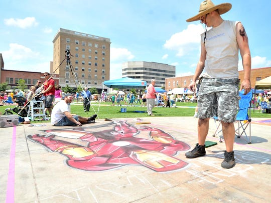 In this file photo. Lenn Soderlund, right, and Luke Ortscheid, both of Wausau, draw a comic book character Ironman during Chalkfest in the 400 block square downtown.