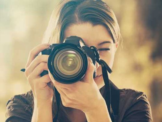 Woman holding a camera up to her face.