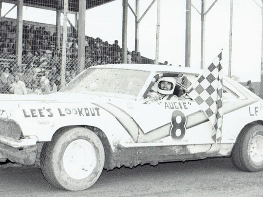 Augie Derenne of Luxemburg shows off some of the spoils of victory after a late-model stock car win at Door County Speedway in 1977.