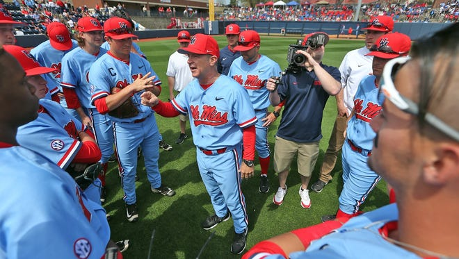 Coach Mike Bianco (center) speaks to his team before a recent game.
