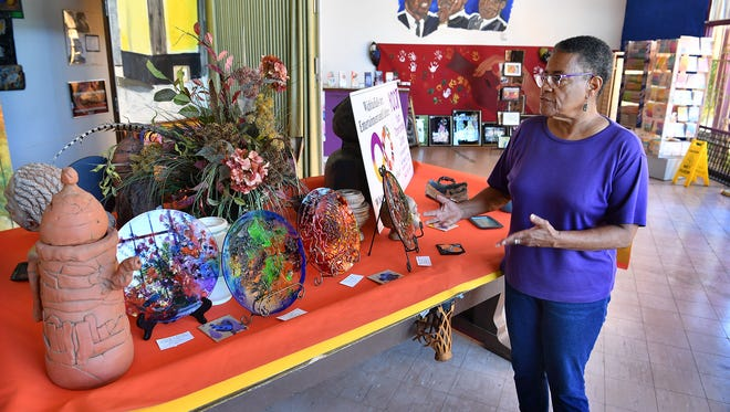 Brenda Jarrett, executive director of the Youth Opportunities Center, talks about a display of local artists' sculpture, glasswork and ceramics. The center's building is in need of a new roof and new air conditioning system.
