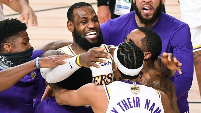 Laker players including LeBron James, center, celebrate the NBA Championship after defeating the Heat in Game 6 of the NBA FInals in Orlando, Florida on Oct. 11, 2020.