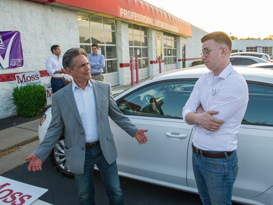 Richard Moss, left, hashes over the campaign results with Caleb Shumaker, right, at First Avenue Car Wash Tuesday.