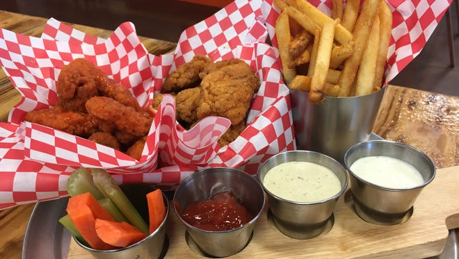 One Stop Kitchen & Bar serves some tasty boneless chicken wings with a side of fries.