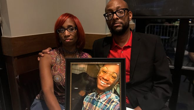 Robert Holmes III, Deborah Holmes and a photo of their son Deion Iman Kennedy.