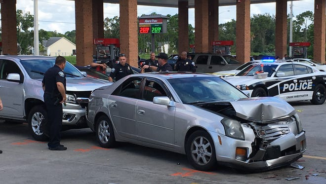 Palm Bay police check out a crash involving at least two cars near the parking lot of a RaceTrack.