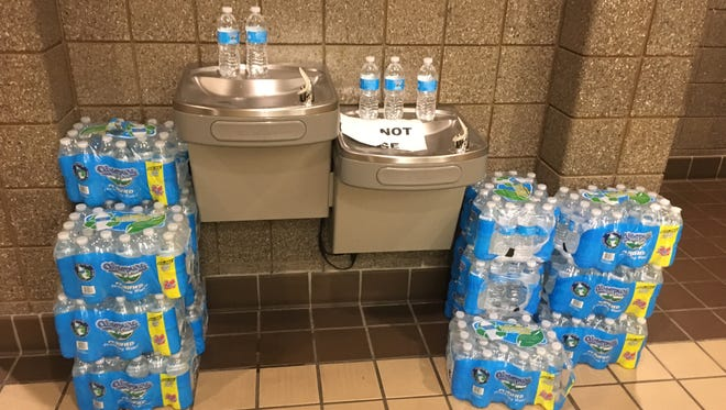 Cases of water surround the the drinking fountain at 67th District Court in Flint on Sept. 21, 2017. Drinking bottled water remains a way a life for Flint residents.