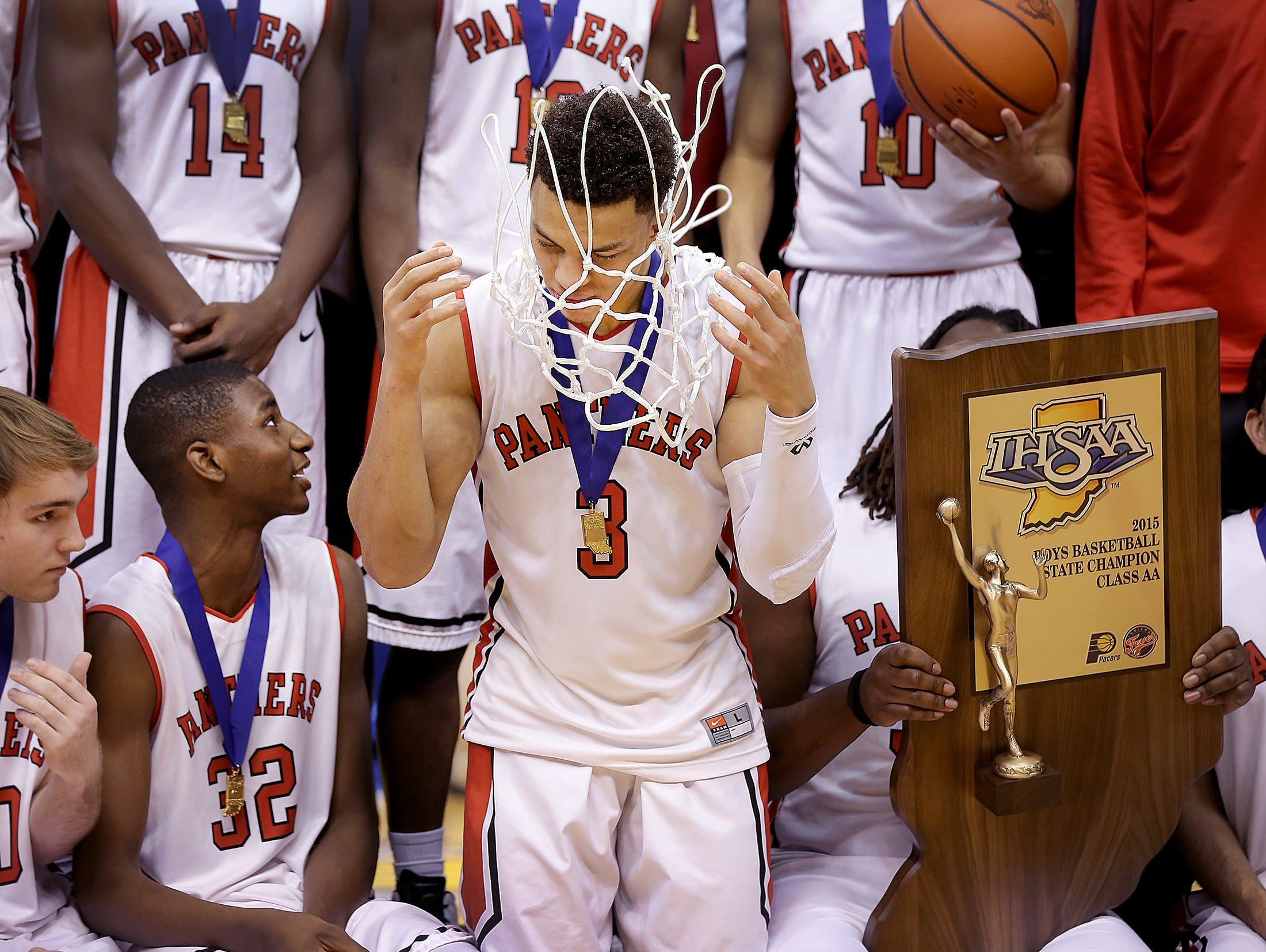 Park Tudor Bryce Moore tosses the net over head as he celebrates with his teammates. The Park Tudor Panther defeated the Frankton Eagles 73-46 to win the IHSAA 2A Boys Basketball State Final Saturday, March 28, 2015, afternoon at Bankers Life Fieldhouse.
