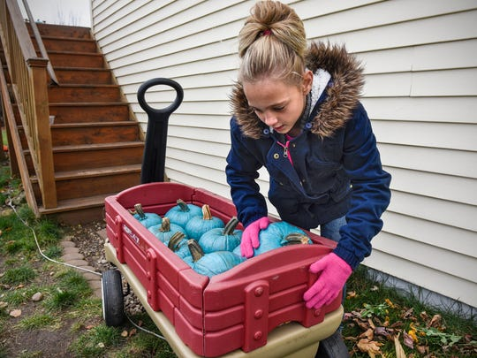 Amara Ross loads specially painted teal pumpkins into a wagon Monday, Oct. 30, at her home in St. Joseph.