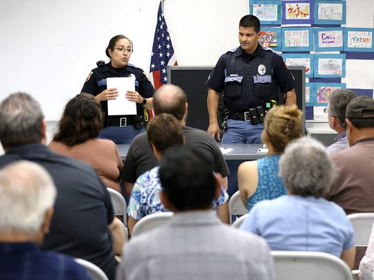 Police Area Representative Officers Imelda Astudillo, left, and Eric Castaneda of the Central Regional Command Center discuss crime statistics with members of the Corbin/Sambrano Neighborhood Association during their meeting July 24 at the Seville Recreation Center. The recreation center was the site of the altercation between a group of teens, a mother and police.