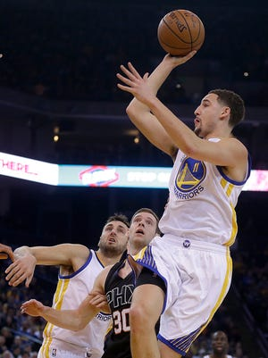 Golden State Warriors' Klay Thompson shoots over Phoenix Suns defender Jon Leuer during the first half of an NBA game Wednesday, Dec. 16, 2015, in Oakland, Calif.