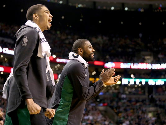 Boston Celtics players Jayson Tatum, left, and Kyrie Irving cheer for their team from the bench during the first half of an NBA basketball game against the Orlando Magic in Boston, Friday, Nov. 24, 2017. (AP Photo/Mary Schwalm)