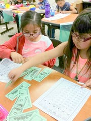 "Two Mescalero students add one hundred dollar bills that teacher Caverly Smith called ""Benjamins"" to create more interest."