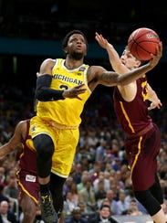 Michigan's Zavier Simpson drives to the basket against