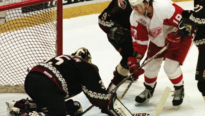 Detroit Red Wings winger Kirk Maltby tries scoring against the defense of Phoenix goalie Nikolai Khabibulin  during the first period in Detroit, Thursday, April 9, 1998. Khabibulin stopped the shot and Maltby received a penalty for goal tender interference. Phoenix's Teppo Numminen and Jeremy Roenick  defend on the play.