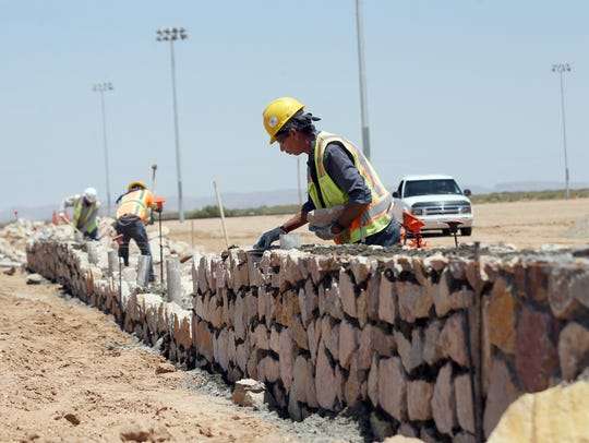 Workers build a rock wall fence Friday around a new