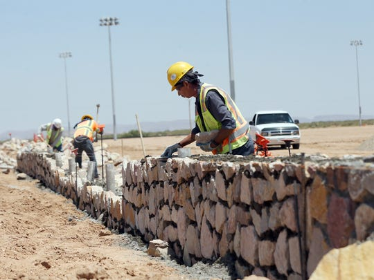 Workers build a rock wall fence Friday around a new sports complex the city is building at Montwood and Honey Dew in far East El Paso.