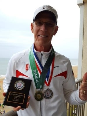 Hopewell Junction's Kevin Dollard poses with his trophies from the USATF National Masters 8-kilometer Championships, held in late March in Virginia Beach.