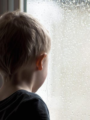 Little boy gazing out of a rainy window looking for daddy