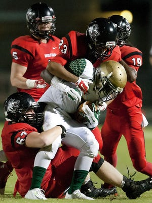 South Fort Myers High School defenders tackle Island Coast running back Van Edwards for a loss Friday (9/12/14) at South Fort Myers.