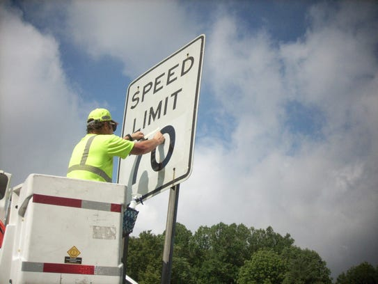 A worker Ronnie Browning puts up a 70 mph sign on Interstate
